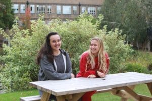 Two young women sitting next to a bench