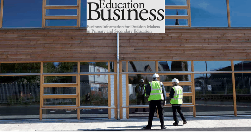 Two builders stand outside an eco school building made of wood and glass.